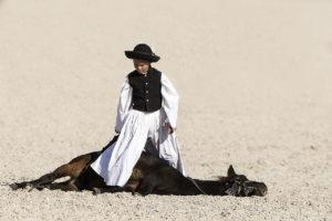 Kind in Tracht steht ueber sienem Pferd